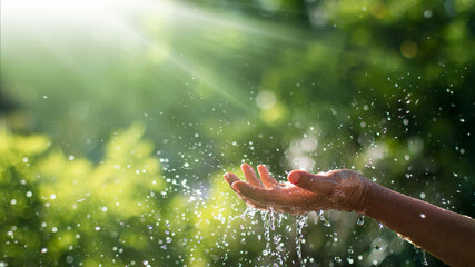 Water pouring and splash in woman hand on nature background, earth day, environment issues