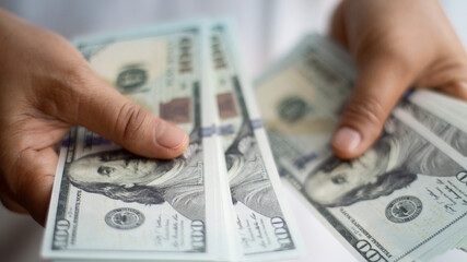 Fototapeta Businessman hand holding dollar bank notes, analysing growth profit from return on investment in financial trade funds and currency exchange. Managing success financial investment in economic trends.