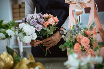 Obraz portrait florist preparing a gift flower on table workspace for customer - fototapety do salonu