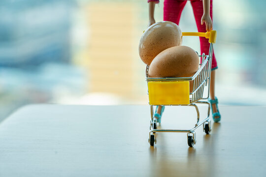 Panic Doll manufactured Woman with trolley Shop cart filled Great Eggs. Hoarding food due to Coronavirus outbreak. Food supplies for the worst case of COVID-19 pandemic. Stockpiling crisis concept.
