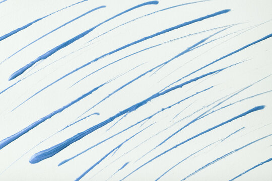 Thin blue lines and splashes drawn on white background. Abstract art backdrop with brush decorative stroke.