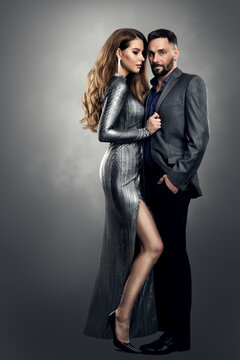 Fashion Woman Man Couple. Luxury Model Girl in Silver Dress holding Man elegant Suit. Provocative Stylish Romantic Pair over Gray Studio Background