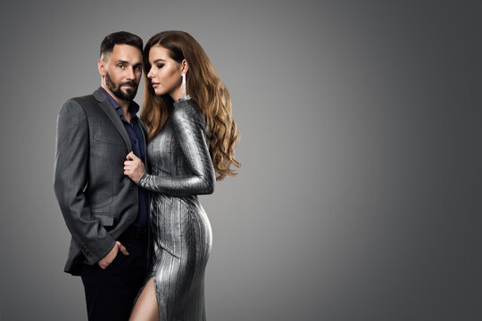 Fashion Couple Man Model Woman. Luxury Glamour Girl in Silver Dress and Elegant man in Suit. Evening Hairstyle and Make up over Gray Background