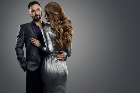 Couple Fashion Woman Man. Beauty Model Hairstyle Back Rear View. Handsome Man in Suit holding Sexy Girl in Silver Dress. Studio Dark Background