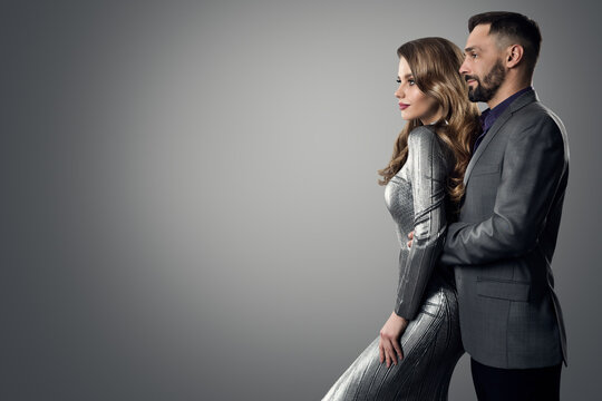 Fashion Stylish Man Woman Profile Side View. Bearded Man in Suit holding Luxury Model. Elegant lady in Silver Dress with Boyfriend over Gray studio Background