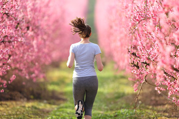 Back view of a runner woman running through a field in spring