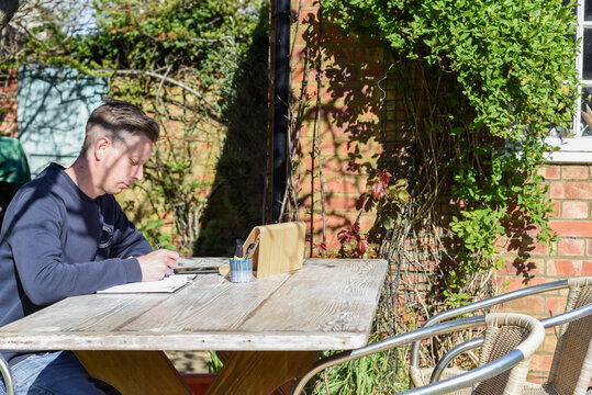 Man writes in a notebook while working from home in a garden