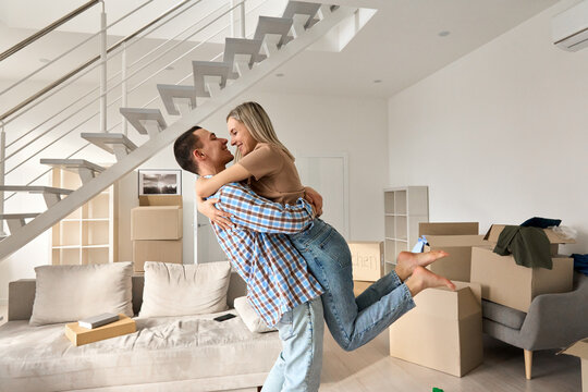 Happy independent couple first time home owners hugging in living room on moving day. Young man and woman apartment buyers celebrating relocation, removal, mortgage, new house purchase concept.
