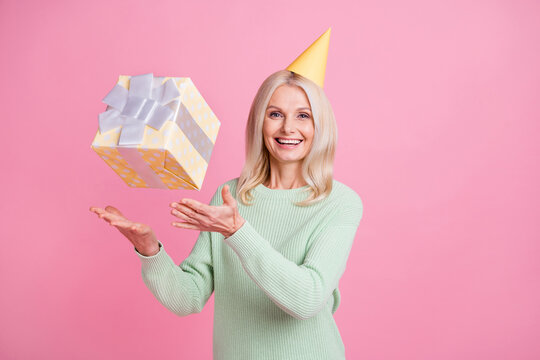 Photo portrait of woman in yellow birthday cone throwing catching present box isolated on pastel pink colored background