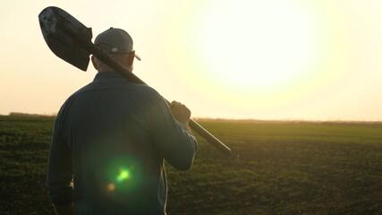 Fototapeta A farmer with a shovel in his hands walks across the field with a shovel in the sun. An agronomist walks on a black fertile plowed land at sunset. Worker with a shovel in a field at sunset.