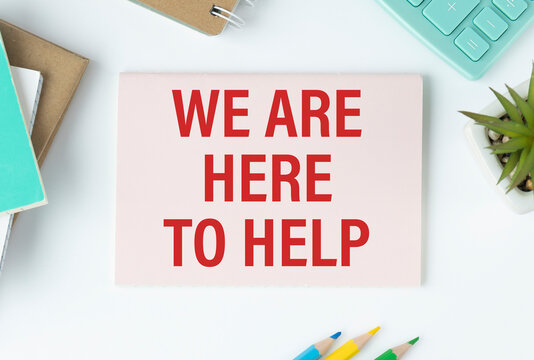 We are here to help, is written on a notepad, on an office desk with office accessories.