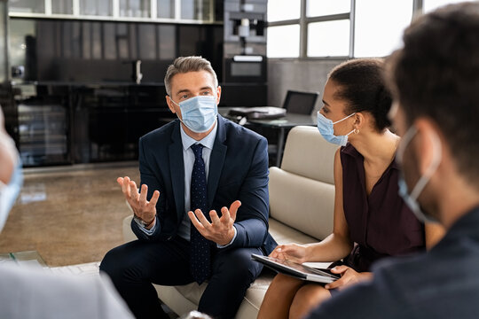 Business people talking in meeting with face mask