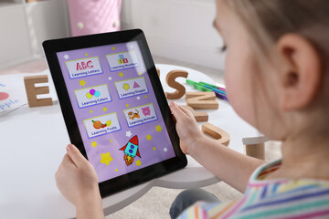 Fototapeta Little girl learning English with tablet indoors at online lesson, closeup
