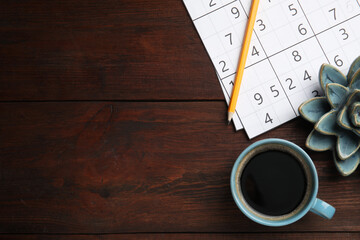 Fototapeta Sudoku, pencil, cup of coffee and decorative succulent on wooden table, flat lay. Space for text