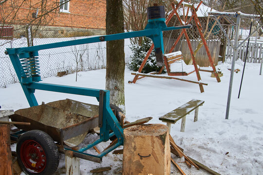 woodcutter in the yard,mechanical wood splitter in the winter in the snow in the yard