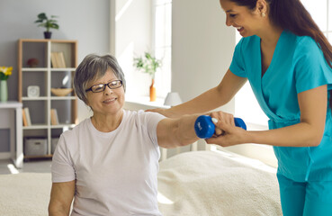 Elderly people care and therapy physical rehab exercises. Smiling professional nurse help patient with elder fit rehabilitation at home. Old lady doing fitness training with dumbbell