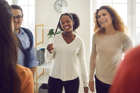Group of happy diverse people communicating in informal work meeting. Happy charming beautiful young black woman listening to coach or colleague at modern business workshop or community meeting