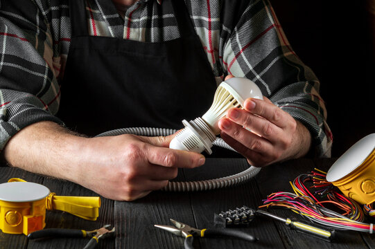 The master electrician turns on the light bulb. Close up of worker hands on the desktop in workshop