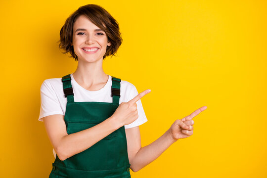 Portrait of pretty cheerful person beaming smile indicate fingers empty space isolated on yellow color background