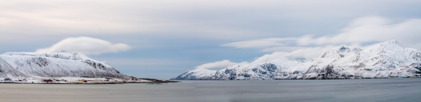Long exposure image of a winter landscape in panorama with snow covered mountains and fjord on the Lofoten in northern Norway