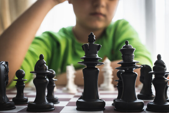 A cute boy with a serious look sits at a table and plays chess. The kid concentrated on the game and thinks where to make his next move. Early development, home educational games for children