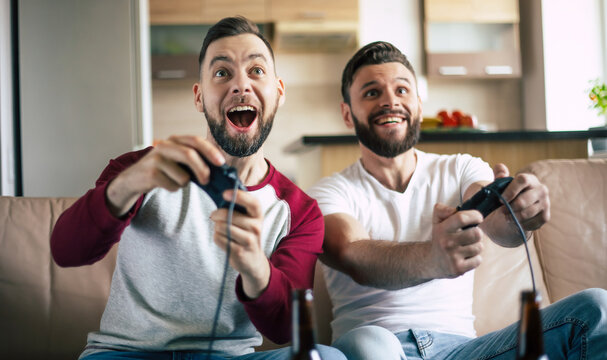 Excited smiling men playing in video games on tv at home on the couch. Friends with joysticks play game with happy emotions on faces