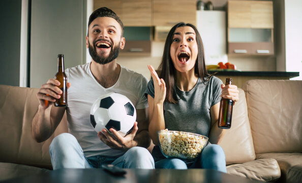 Happy fans couple is watching some football match in TV with snacks, beers and ball on the couch