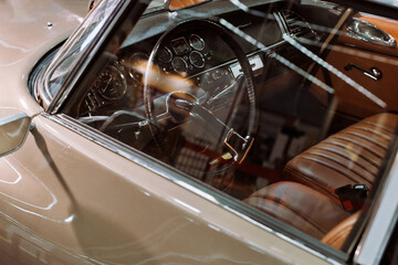 Fototapeta Interior of a beige classic car with leather seats at a car show or exhibition obraz