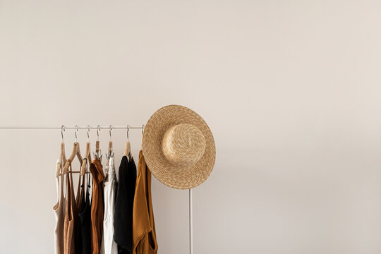 Aesthetic minimalist fashion influencer blog composition. Stylish pastel summer female clothes, dress, tops, t-shirts, straw hat on clothing rack against white wall. Fashion women wear