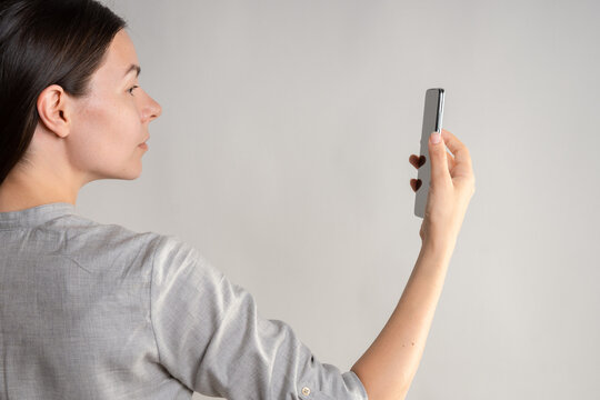 woman holds the smartphone in front of her eyes and unlocks the phone via face id.