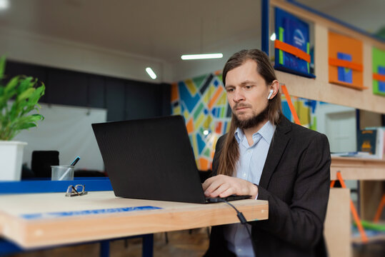 A man working on a laptopt in a colorful co-working