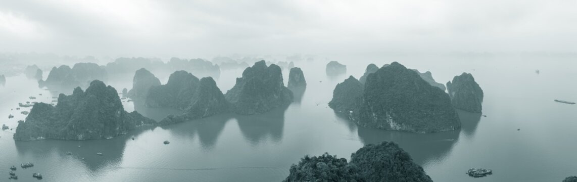 Aerial view over misty Ha Long Bay and tall rock pillars