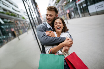 Fototapeta Cheerful successful happy young lovely couple with shopping bags traveling and laughing