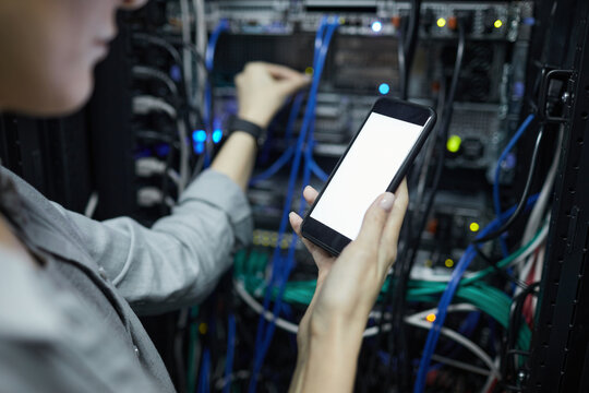 Close up of female network technician holding smartphone with blank screen while connecting cables in server cabinet, copy space