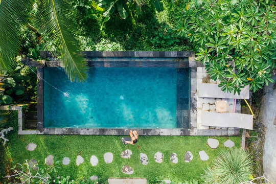 Beautiful girl relaxing outdoor in her garden with swimming pool. Summer concept about lifestyle,beauty, vacations and real estates. Aerial drone view