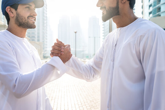 Two young men going out in Dubai. Friends wearing the kandura traditional male outfit and baseball hat in Marina