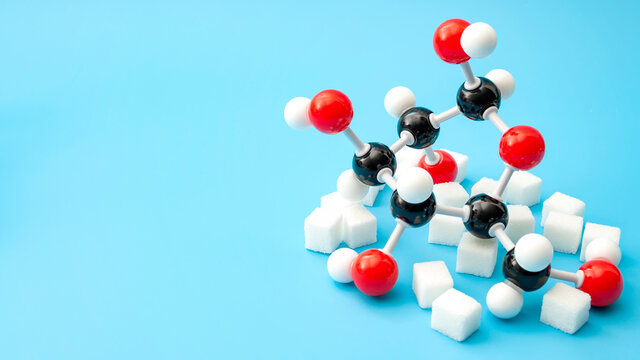 Simple sugars, diabetes awareness and chemical structure of carbohydrates concept with plastic model of the glucose molecule and sugar cubes isolated on blue background with copy space