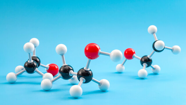 Molecular structure of chemical compounds and organic chemistry concept with educational plastic model of ethanol molecule isolated on blue background