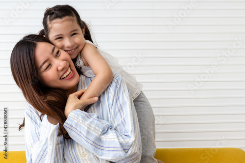 Little girl hug mom from back. Looking at camera and smile. Happy family and mother's day concept. Asian woman and Caucasian girl in pajamas playing together at home.