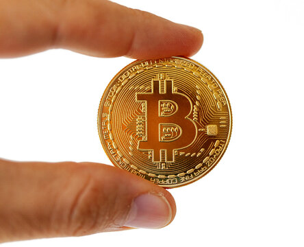 A Bitcoin coin between the fingers. Subject isolated on white background.