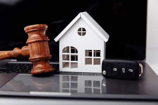 Wooden judge gavel with house and car key on a laptop. Online auction or bidding concept