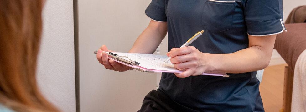 カウンセリング クリニック 問診票に書き込むシーン