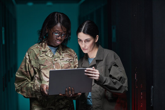 Waist up portrait of two young women wearing military uniform using laptop while standing in server room, copy space