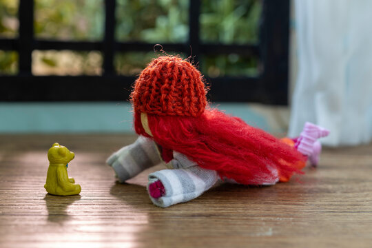 Doll teenager with red hair and a knitted hat lying on a wooden floor talking to a plastic teddy bear.  Sun shining through the window.