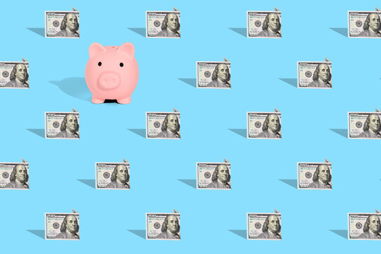 . Pattern of American dollar banknotes and pink piggy bank on bright blue background. The concept of financial savings and miscellaneous transactions.