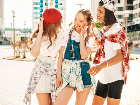 Portrait of three young beautiful smiling hipster female in trendy summer clothes. carefree women posing on the street background.Positive models having fun and going crazy