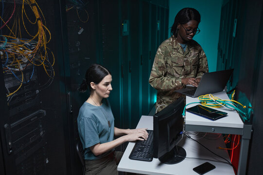 Portrait of two military young woman using computers while working together in server room and setting up network, copy space