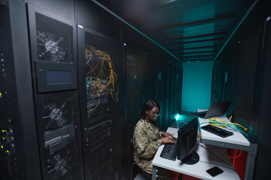 Wide angle portrait of young African-American woman wearing military uniform using computer while setting up network in server room, copy space