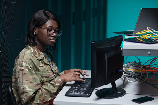 Side view portrait of young African-American woman wearing military uniform using computer while working in server room