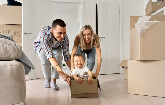Overjoyed excited happy householders renters tenants parents pushing carton box with kid riding in new apartment, having fun in their first moving day to real estate property. New home concept.
